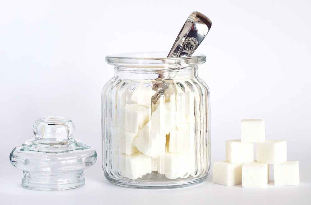close up photo of sugar cubes in glass jar